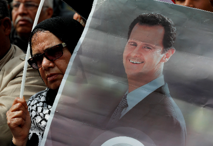 En demonstrant har en plakat av Syrias president Bashar al-Assad																		AP Photo/Hussein Mall